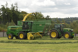 John Deere 7700 SPFH filling a Smyth Trailers Super Cube Field Master Trailer drawn by a John Deere 6155R Tractor