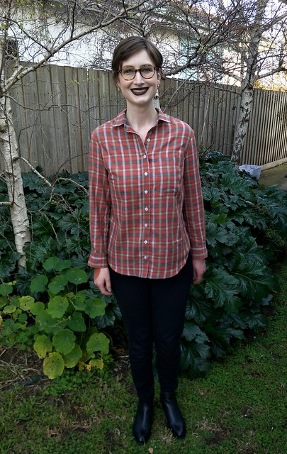 Woman stands in front of a garden fence, wearing a red check button up shirt, black pants and ankle boots. She is smiling.