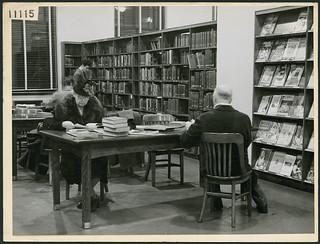 Woman wearing a hat and a coat with a fur collar reads at a table in the London Public Library, Ontario / Femme portant un chapeau et un manteau avec un col en fourrure, bibliothèque publique de London (Ontario)
