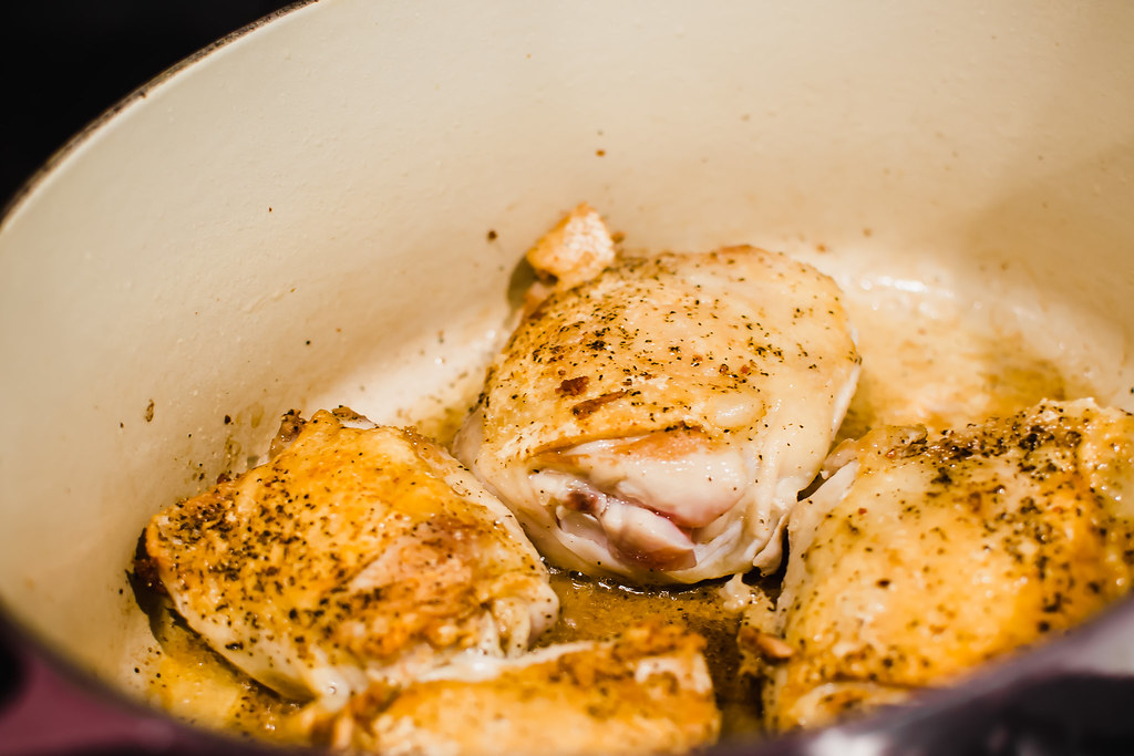 Begin making Julia Child's coq au vin by searing chicken in bacon fat before adding other aromatics.