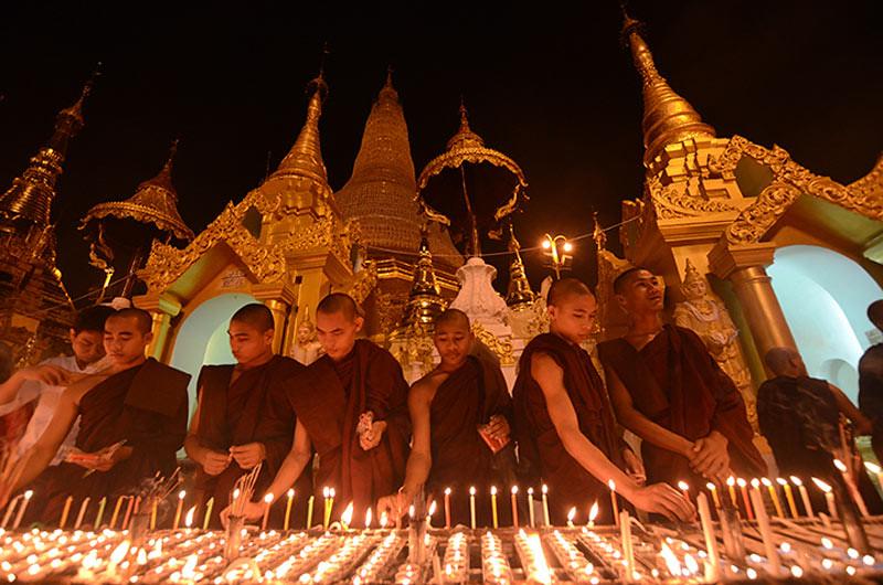 Para bhikkhu dan samanera menyalakan lilin pada malam Purnama Thadingyut yang merupakan akhir masa vassa dan awal Kathina