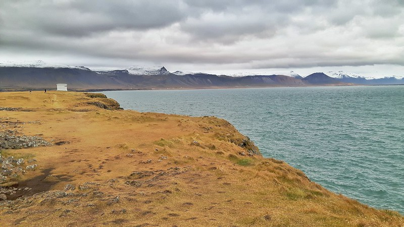 Grassy cliffs in Arnarstapi, Iceland with blue waters and snow covered mountains behind.