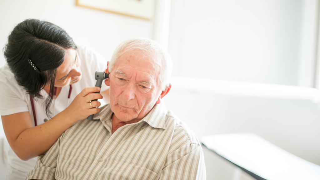 A patient has his ears checked in a medical setting.