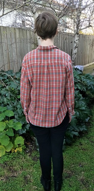 Woman stands in front of a garden fence, wearing a red check button up shirt, black pants and ankle boots. Her back is to the camera.