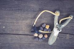 Sling shot. A wooden sling shot on wood. Processed in old film filter, vintage style.