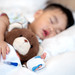 Asian baby sleep with teddy bear and saline on the bed in Hospital
