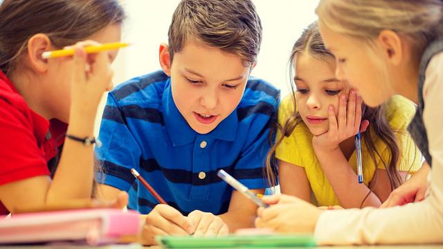 Children write on notebook together