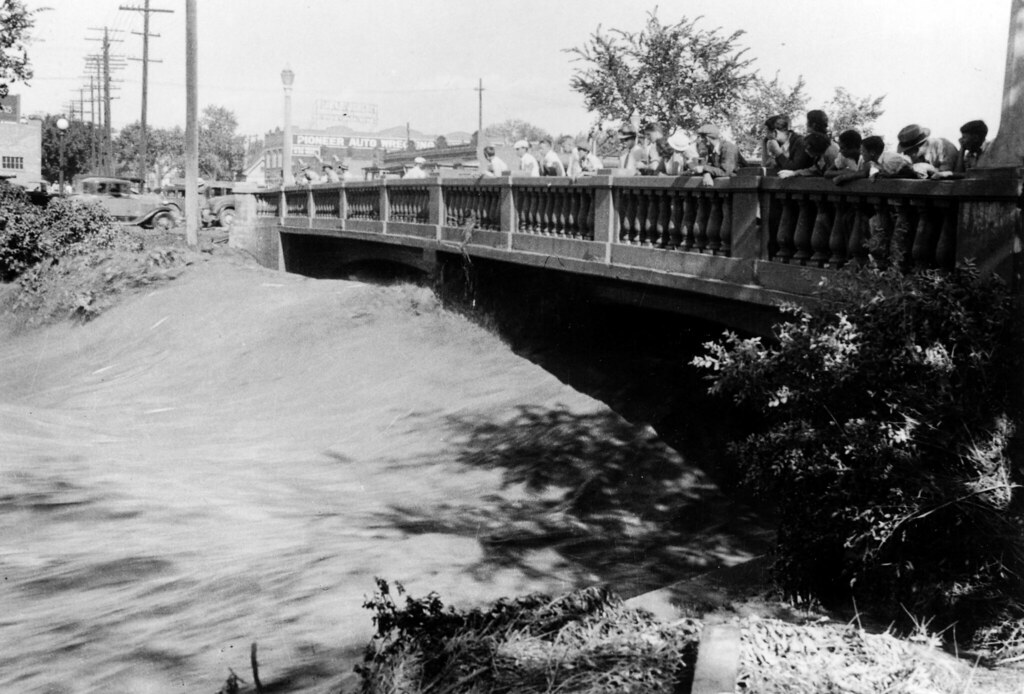 Cherry Creek flood in Denver, Colorado after the Castlewood Canyon Dam break. People stand on the 13th Avenue bridge and watch torrents of water. 3 August 1933