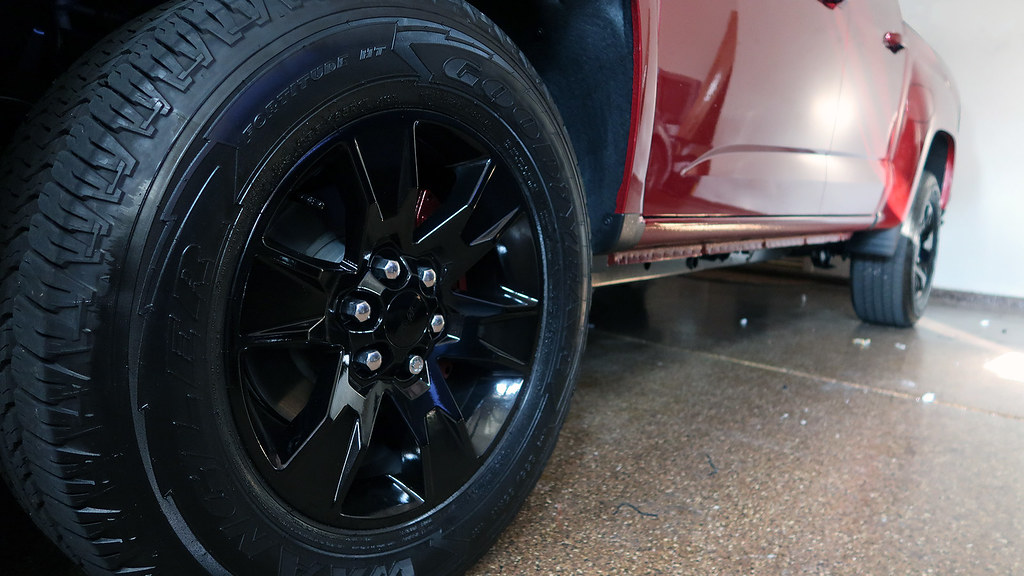 Close-up of painted black wheels and red quartz tintcoat brake calipers