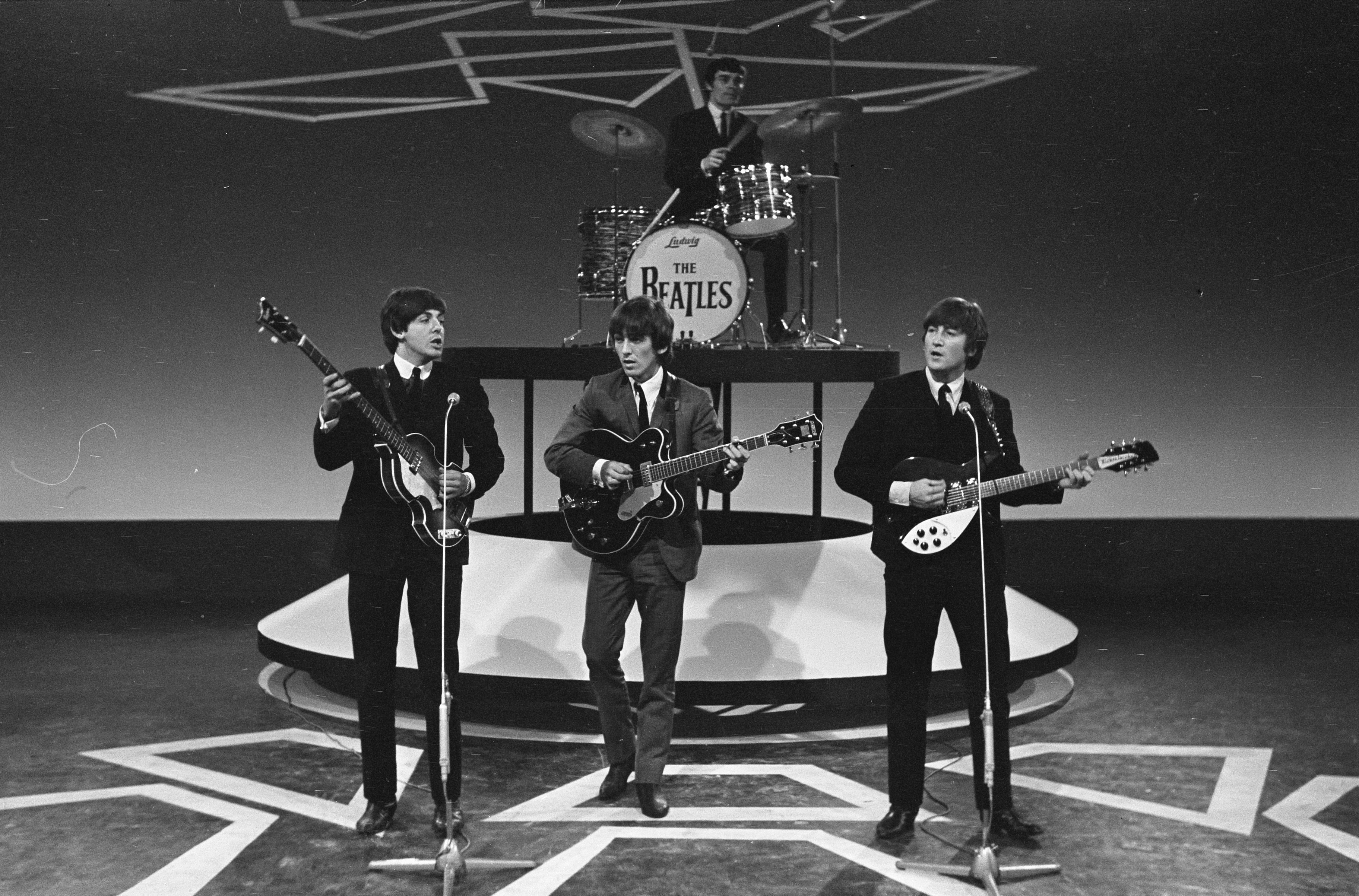 Television appearance by John Lennon (right) with The Beatles at Treslong, Hillegom, Netherlands on June 5, 1964. Jimmy Nichol is on drums, substituting for Ringo Starr at this performance.