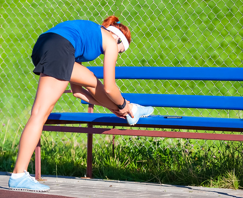 Sport Concepts. Full Length Portrait of Sportive Girl in Outdoor Outfit Having Legs Stretching Exercises Near Long Bench Outdoors While Listening to Music.