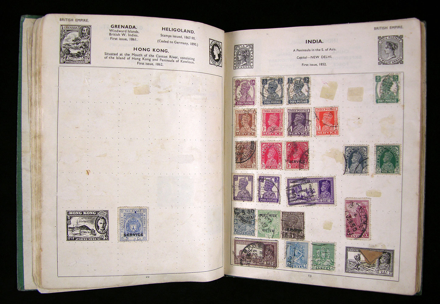 Front cover and pages 22-23 (with stamps from India) of John Lennon's green Mercury stamp album.