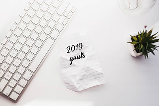 "Top view of flat lay with keyboard, plant and paper with ""2019 goals"". New year concept. 