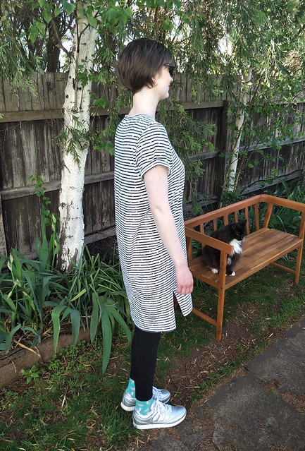 A woman stands in front of a garden fence. She wears a stripe knit tee dress with black leggings, silver runners and big tortoiseshell sunglasses. A cat sits on a bench behind her.