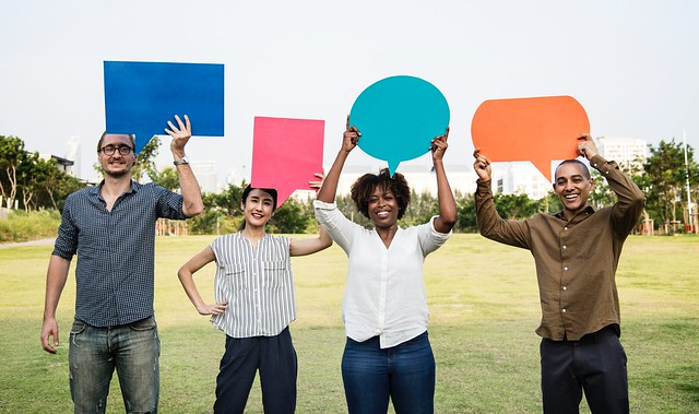Casual style image with people holding up multi colours speech bubbles