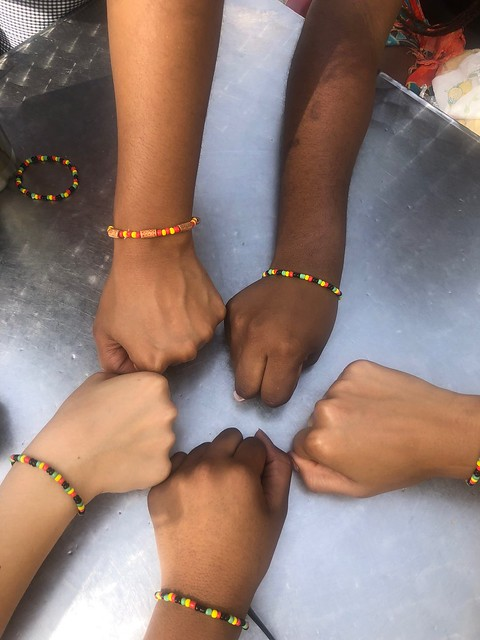 Hands of students wearing matching bracelets.
