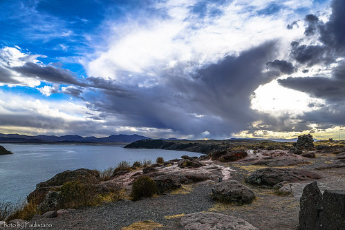 travel peru andes landscape nature altiplano mountains mountainside sillustani sky cloud umayo lake water rock stone grass