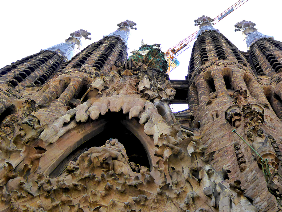 A view of one of the three exceptional facades of the Basilica de la Sagrada Familia, which highlights many of the Christian themes incorporated within the Expiatory Temple of the Holy Family located in Barcelona