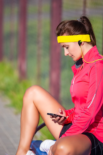 Sport Ideas and Concepts. Relaxed Caucasian Sportswoman in Outdoor Sport Outfit Having Break and Listening to Music from Smartphone. Sitting on Bench with Legs Folded.