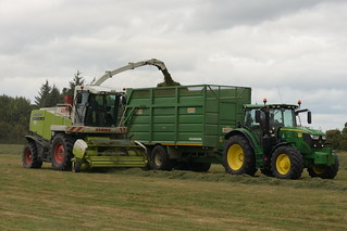Claas Jaguar 890 SPFH filling a Smyth Trailers Field Master Trailer drawn by a John Deere 6155R Tractor