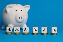 Nasdaq text with piggy bank