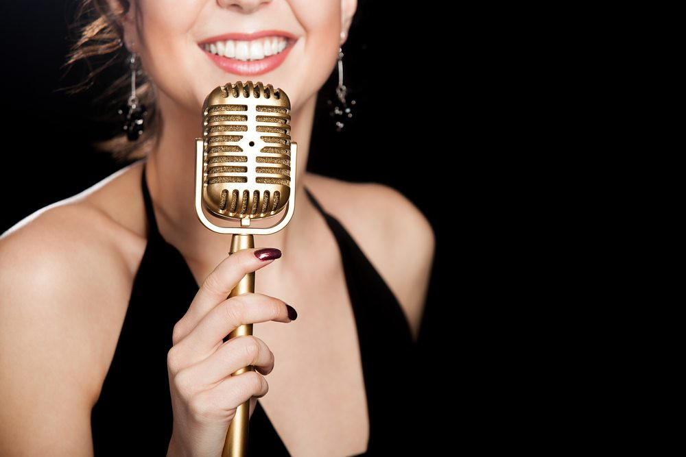 Photo of confident singer performing with classica microphone