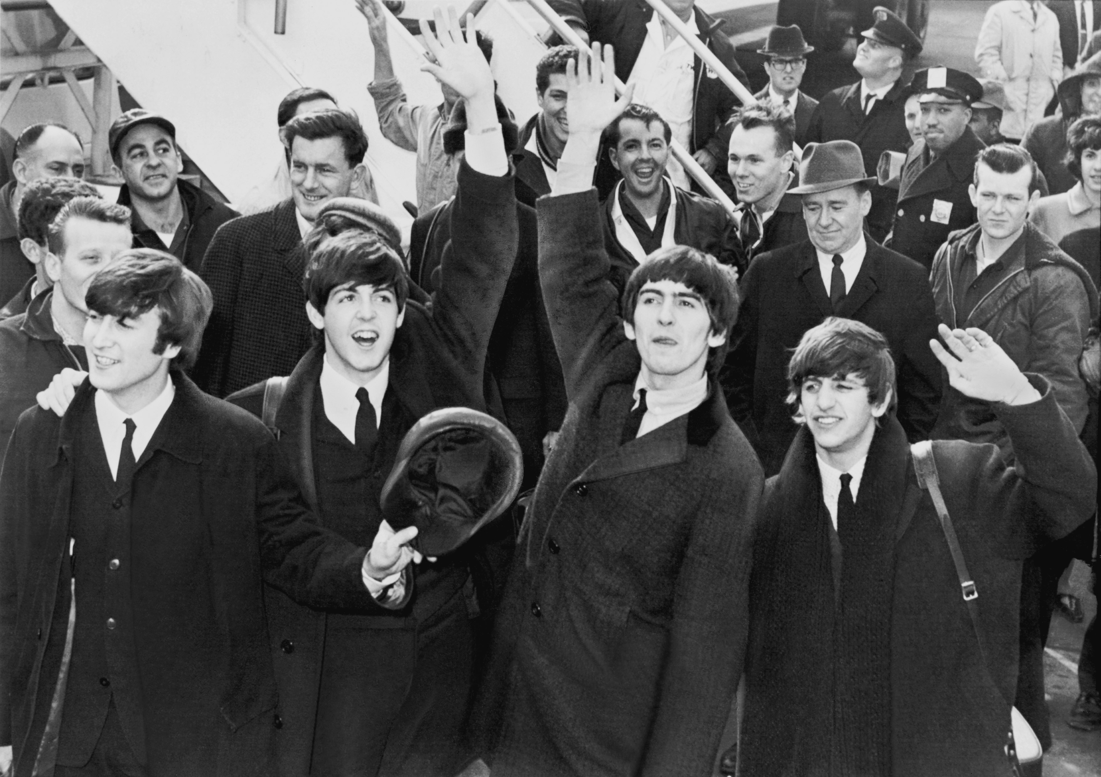 The Beatles wave to fans after arriving at John F. Kennedy International Airport, New York on February 7, 1964. Universal Press International photo. This image is available from the United States Library of Congress's Prints and Photographs division under the digital ID cph.3c11094.