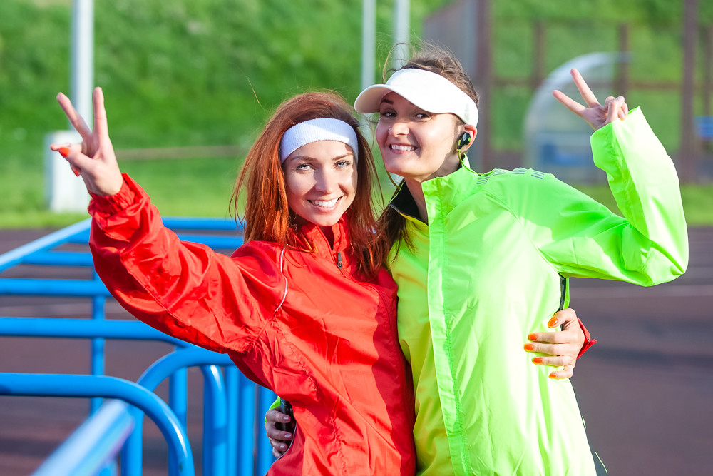 Two Positive and Smiling Caucasian Sportswomen in Outdoor Outfit Having Good Time and Posing With V-Signs On Camera.