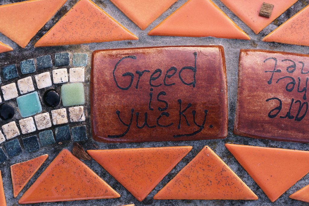 A tile says 'Greed is yucky' on the dragon statue at the Irvington School in the Irvington neighborhood of Portland, Oregon