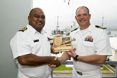 SUVA, Fiji (Oct. 15, 2018) Cmdr. Andy Strickland, commanding officer of the guided-missile destroyer USS Shoup (DDG 86), exchanges gifts with Capt. Humphrey Tawake, commander of the Fiji Navy, during an office call. Shoup is participating in the Oceania Maritime Security Initiative (OMSI) program, a Secretary of Defense program leveraging Department of Defense assets transiting the region to increase the Coast Guard's maritime domain awareness, ultimately supporting its maritime law enforcement operations in Oceania. (U.S. Navy photo by Mass Communication Specialist 2nd Class William Collins III/Released)