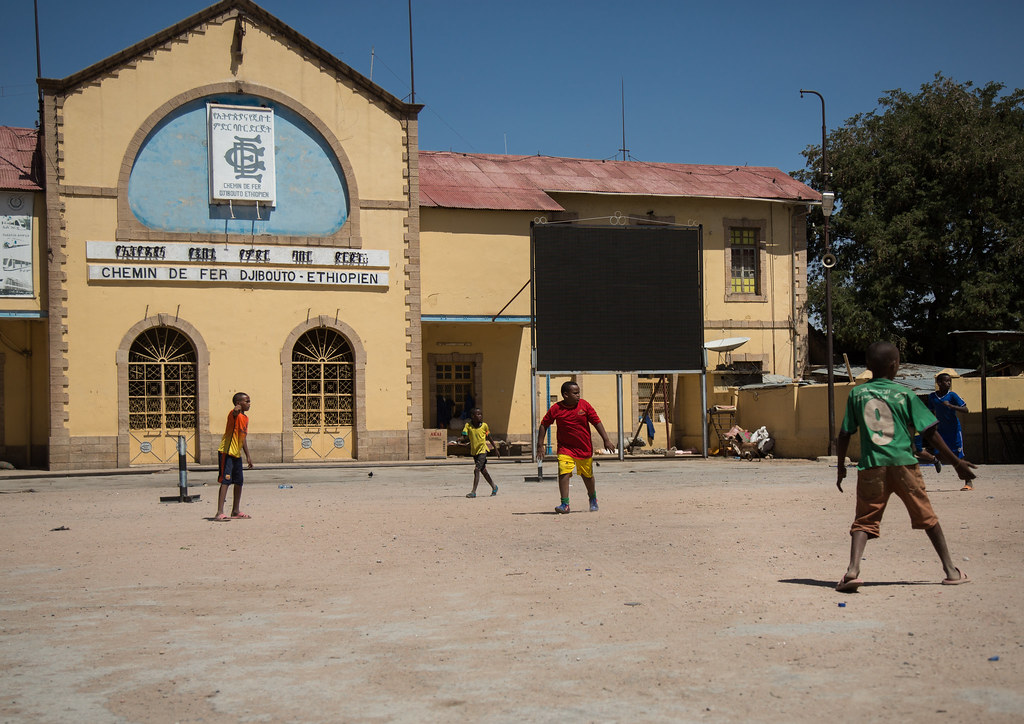 Kids playing football in front of the station of the ethio