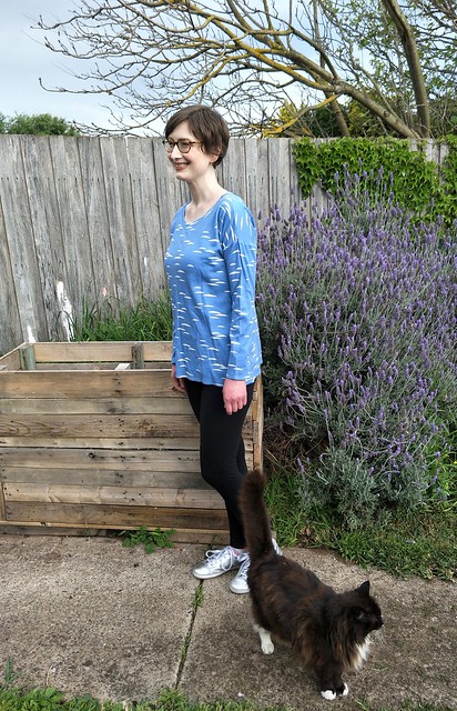 A woman stands in front of a garden fence. She wears a blue long sleeve tee with white cloud-like print, black leggings and silver runners. A cat meanders by.