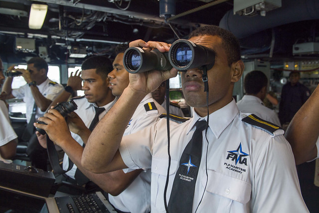 SUVA, Fiji (Oct. 16, 2018) A student of Fiji Maritime Academy uses binoculars in the pilot house of the guided-missile destroyer USS Shoup (DDG 86) during a tour as part of Shoup's port visit in Suva. Shoup is participating in the Oceania Maritime Security Initiative (OMSI) program, a Secretary of Defense program leveraging Department of Defense assets transiting the region to increase the Coast Guard's maritime domain awareness, ultimately supporting its maritime law enforcement operations in Oceania. (U.S. Navy photo by Mass Communication Specialist 2nd Class William Collins III/Released)