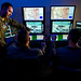 Maj. Michael, a remotely piloted aircraft fundamentals course instructor pilot, right, discusses a training mission utilizing the Predator Reaper Integrated Mission Environment simulator with Tech. Sgt. Ben, an enlisted pilot student, and Staff Sgt. James, a basic sensor operator course instructor at the 558th Flying Training Squadron at Joint Base San Antonio, Texas Jul. 17, 2018. Both officer and enlisted RPA student pilots spend 85 days in the RPA Instrument Qualification course (RIQ) and 30 days in the RPA Fundamentals Course (RFC) at the 558th FTS, during the second phase of the Air Education and Training Commandâs RPA pilot curriculum. Last Names removed and obscured for OPSEC. (U.S. Air Force photo by J.M. Eddins Jr.)