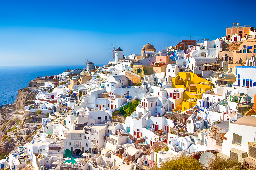 Amazing Picturesque Santorini Island in Greece. Wonderful Daylight Scenery with Traditional Greek White Architecture. Located in Oia Village and Ochre Domed Church.