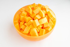 Diced butternut squash in a orange bowl on white background
