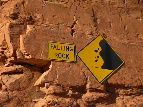 A warning sign on a red rock cliff in Mexican Hat, Utah