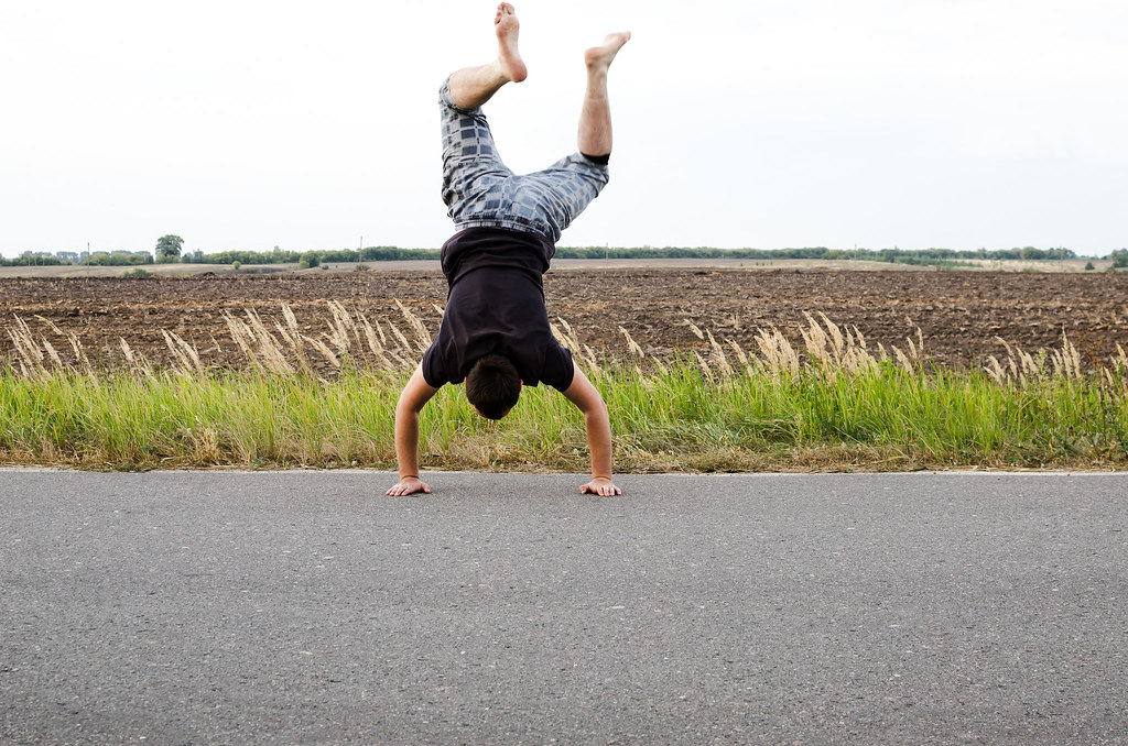 Man does handstand on the hand on the road