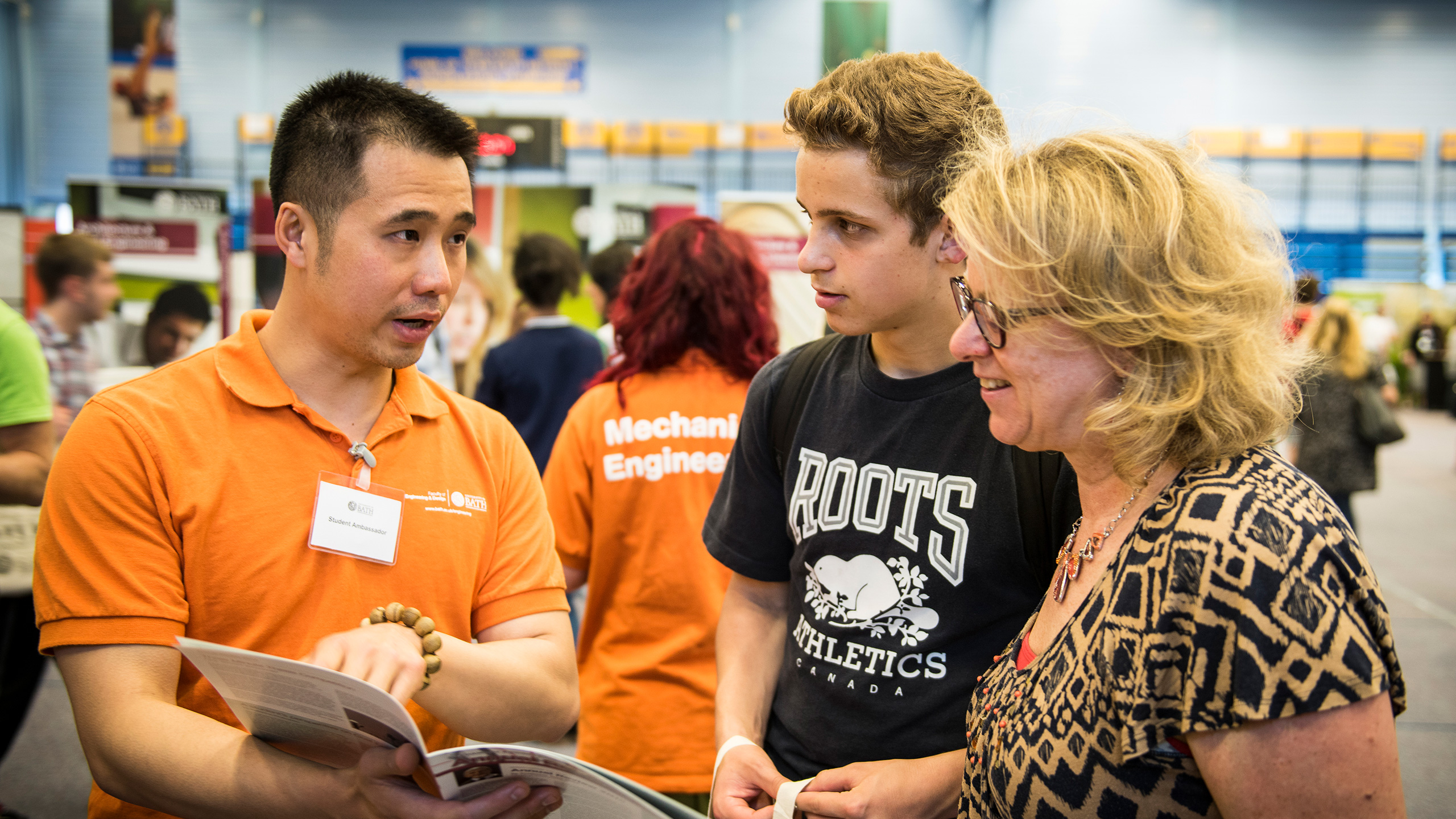 A mechanical engineering student ambassador talks with a prospective student and his mother