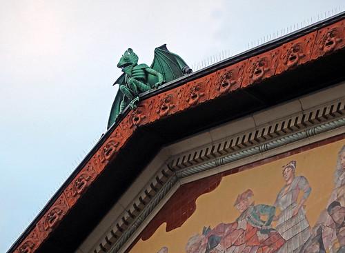 A copper gargoyle cheekily sits atop a building in Aarhus, Denmark