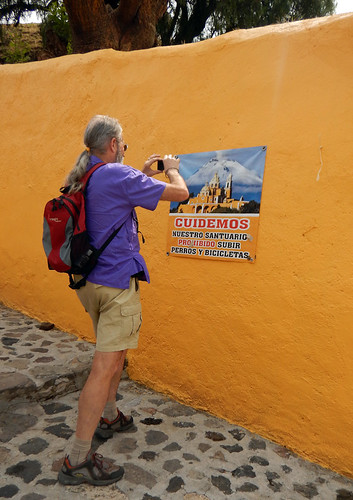 Al taking a photo of the advertising of the church with the volcano looming over it in Cholula, Mexico