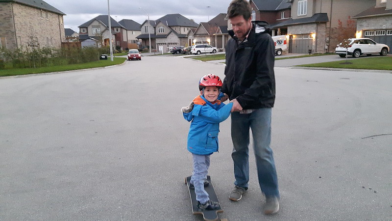 Terry teaching a boy to ride a skateboard.