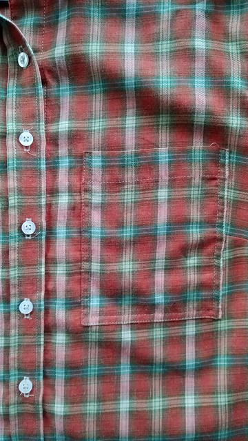 Close up of a shirt buttonband and pocket, sewn in a red check. All the plaids match.