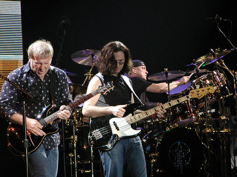 Canadian rock band Rush, performing in Milan, Italy. Left to right: Alex Lifeson, Geddy Lee, Neil Pert. Photo taken by Enrico Frangi on September 21, 2004.