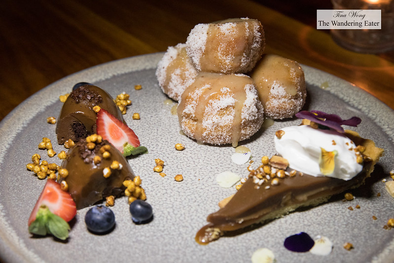 Dessert plate - chocolate cake, caramel tart with bee pollen and fried doughnut holes topped with caramel sauce