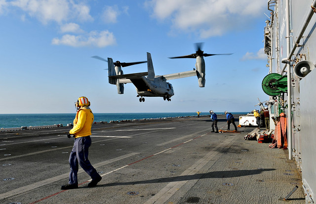 "EAST CHINA SEA (Oct. 23, 2018) An MV-22 Osprey assigned to the ""Flying Tigers"" of Marine Medium Tiltrotor Squadron 262 reinforced lands on the flight deck of amphibious assault ship USS Wasp (LHD 1). An Air Force variant CV-22 Osprey, assigned to the 353rd Special Operations Group, detachment 1,  and Marine Corps MV-22 Ospreys are conducting joint training aboard Wasp to enhance joint interoperability at sea. Wasp, Flagship of the Wasp Amphibious Ready Group, is operating in the Indo-Pacific to enhance interoperability with partners and serve as a ready-response force for any type of contingency. (U.S. Navy photo by Mass Communication Specialist 1st Class Daniel Barker)"