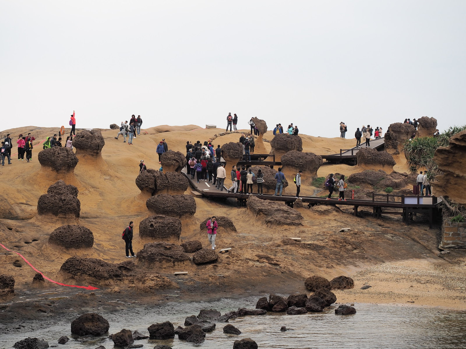 Tourists posing and taking photo at Yehliu Geopark (野柳地質公園) with the Queen's Head