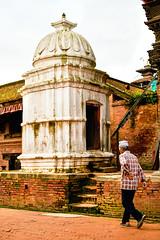 Man walking by a Hindu Shrine in Bhaktapur, Nepal