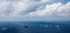 PHILIPPINE SEA (Nov. 8, 2018) The aircraft carrier USS Ronald Reagan (CVN 76), left, and the Japanese helicopter destroyer JS Hyuga (DDH 181), right, sail in formation with 16 other ships from the U.S. Navy and Japan Maritime Self-Defense Force (JMSDF) as aircraft from the U.S. Air Force and Japan Air Self-Defense Force fly overhead in formation during Keen Sword 2019. Keen Sword 2019 is a joint, bilateral field-training exercise involving U.S. military and JMSDF personnel, designed to increase combat readiness and interoperability of the Japan-U.S. alliance. (U.S. Navy photo by Mass Communication Specialist 3rd Class Erwin Jacob V. Miciano)