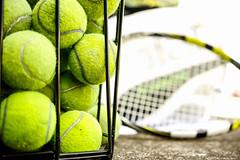 Old tennis balls in a tennis ball basket